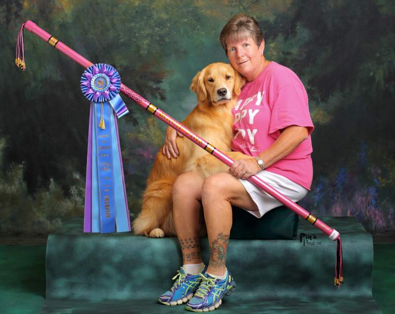 The same lady sitting beside two-year-old golden retriever, Pink in setting with a mottled green and black background and holding pink-colored PVC autograph bar with large rosette award ribbon hanging from one end-setting in a professional portrait